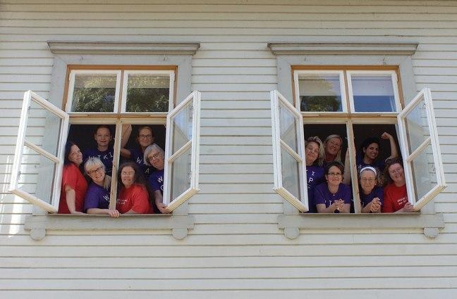 Tio kvinnliga lägerdeltagare tittar ut genom två fönster.
